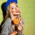 Sexy suntan girl in short jeans shorts against gre young blue baseball cap green brick wall holds round orange lollipop Royalty Free Stock Images