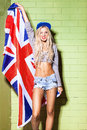 Sexy suntan girl in short jeans shorts against green brick wall young beautiful holds britain flag Royalty Free Stock Photo