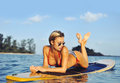 Sexy surfer girl lying on a surfboard in the sea Royalty Free Stock Photo
