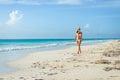 Sexy tanned woman in bikini on tropical natural beach enjoying idyllic and caribbean summer vacation fit brunette enjoying a walk Stock Image