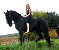 Sexy teenager and her black stallion Stock Images