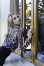 Sexy urban woman leaning against window color portrait of blonde in setting wearing animal print chiffon blouse black skirt Royalty Free Stock Photos