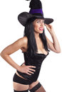 Sexy witch a in a black corset stockings and hat on white background Stock Photo
