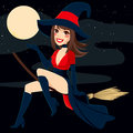Sexy witch flying brunette on a broom over a full moon night background Royalty Free Stock Photography