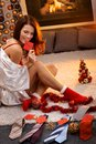 Sexy woman arranging christmas gifts in silk gown and socks tie with name tag for men Stock Photos
