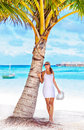 Sexy woman on the beach standing near palm tree relaxation outdoors luxury tropical resort summer vacation maldives Royalty Free Stock Images