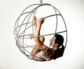 Sexy woman in a beige swimsuit on a metal swing on a white background