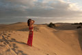 Sexy woman belly dancer arabian in desert dunes at the afternoon Royalty Free Stock Photography