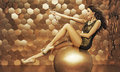 Sexy woman on a big ball gold Stock Photography