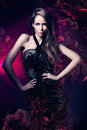 Sexy woman in black dress on dark magenta background Royalty Free Stock Images