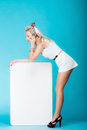 Sexy woman with blank presentation board banner sign talking phone retro style blonde in full length girl holds billboard copy Stock Image