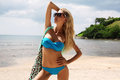 Sexy woman with blond hair in bikini and sunglasses relaxing on beach Royalty Free Stock Photo