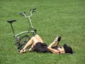 Sexy woman chilling on grass the laying her back in central park new york city nyc with a folded bike at her feet Stock Photos