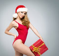 A sexy woman in Christmas clothes holding a present Royalty Free Stock Photo