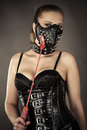 Sexy woman in corset and mask with spikes isolated on gray background Stock Photography