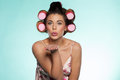 Sexy woman in curlers blowing a kiss beautiful large pink romantic across her palm at her sweetheart Stock Images