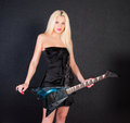 Sexy woman in dress with electric guitar over dark background Royalty Free Stock Photo