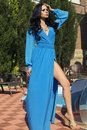 Sexy woman in elegant blue dress posing at villa fashion photo of glamour model with black hair beside a swimming pool Stock Photo