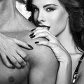 Sexy woman embrace naked man shoulder black and white women men bdsm Stock Image