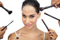 Sexy woman encircled by make up brushes on white background Stock Photos