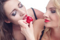 Sexy woman feeding lesbian lover with strawberry