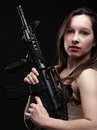 Sexy woman girl holding an assault rifle black background Royalty Free Stock Images