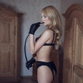 Sexy woman in gloves bite whip motel room Stock Photos