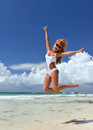 Sexy woman happy jumping relaxing on tropical beach send young with long windy hair in white bikini and sunglasses Stock Photography