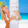 Sexy woman hug palm tree blond with frangipani flower in head on beautiful seascape background luxury spa resort enjoying summer Stock Images