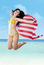 Sexy woman jumping with holding american flag young beautiful happy while at beach Stock Photos