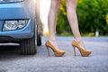 Sexy woman with long legs standing near the car on the road Royalty Free Stock Photo