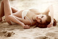 Sexy woman lying in the sand Royalty Free Stock Images