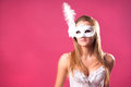 Sexy woman in mask beautiful sensual pretty young white lace underwear and with feather over pink background copy space Stock Image