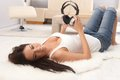 Sexy woman relaxing at home young lying on floor holding headphones smiling happy Royalty Free Stock Image