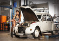 A sexy woman repairing a retro car in a garage