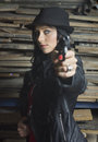 Sexy woman with revolver and leather jacket a blue eyes black hair wearing a a hat holding a looking dangerous Royalty Free Stock Photography