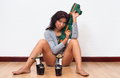 Sexy woman sitting on the floor holds toy gun Royalty Free Stock Photo