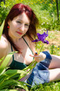 Sexy woman sitting in the garden near violet flower Royalty Free Stock Photo