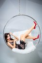 Sexy woman suspended from an aerial hoop sitting in a chair round Royalty Free Stock Images