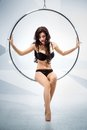Sexy woman suspended from an aerial hoop sitting in a chair round Royalty Free Stock Photo