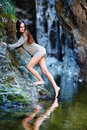 Sexy woman trying the water with her foot portrait of a young leaning on mountain rock close to a mountain waterfall Royalty Free Stock Photo