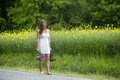 Sexy woman walking in barefeet a beautiful wearing a white dress walks down the road carrying her boots and flowers from a sad Royalty Free Stock Photography