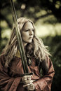Sexy woman warrior with sword outdoor beautiful blond Royalty Free Stock Photography