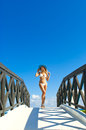 Sexy woman in white bikini standing on small bridge in sunny day wooden Stock Photo