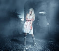 Sexy woman zombie stands in ruins among the the mist and moonlight Royalty Free Stock Photography