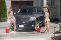 Sexy women wash a black truck while wearing bikinis in the spring Royalty Free Stock Photos
