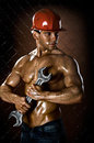 Sexy workman the beauty muscular worker man in safety helmet with big wrench in hands on netting fence background Stock Photos