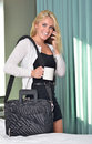 Sexy young blonde business woman in bedroom black dress and white sweater walking out of with briefcase cup of coffee and talking Royalty Free Stock Photography