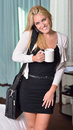 Sexy young blonde business woman in bedroom black dress and white sweater walking out of with briefcase cup of coffee and talking Stock Photos