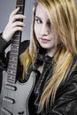 Sexy young blonde dressed in black leather holding electric guitar rockstar Royalty Free Stock Photos